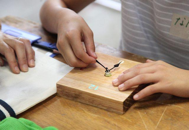 木の時計づくり。広葉樹のきれいな木目の板に、時間を書いて針をセットして……