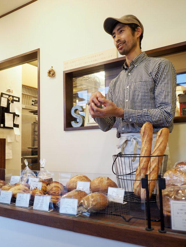 店頭でパンの魅力を説明するご主人