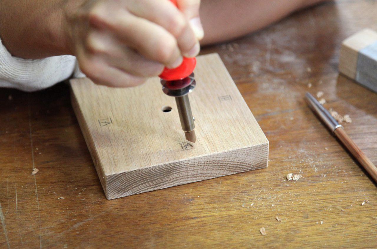 アラビア数字を鉛筆で下書きして、半田ごてで焼いていくところ