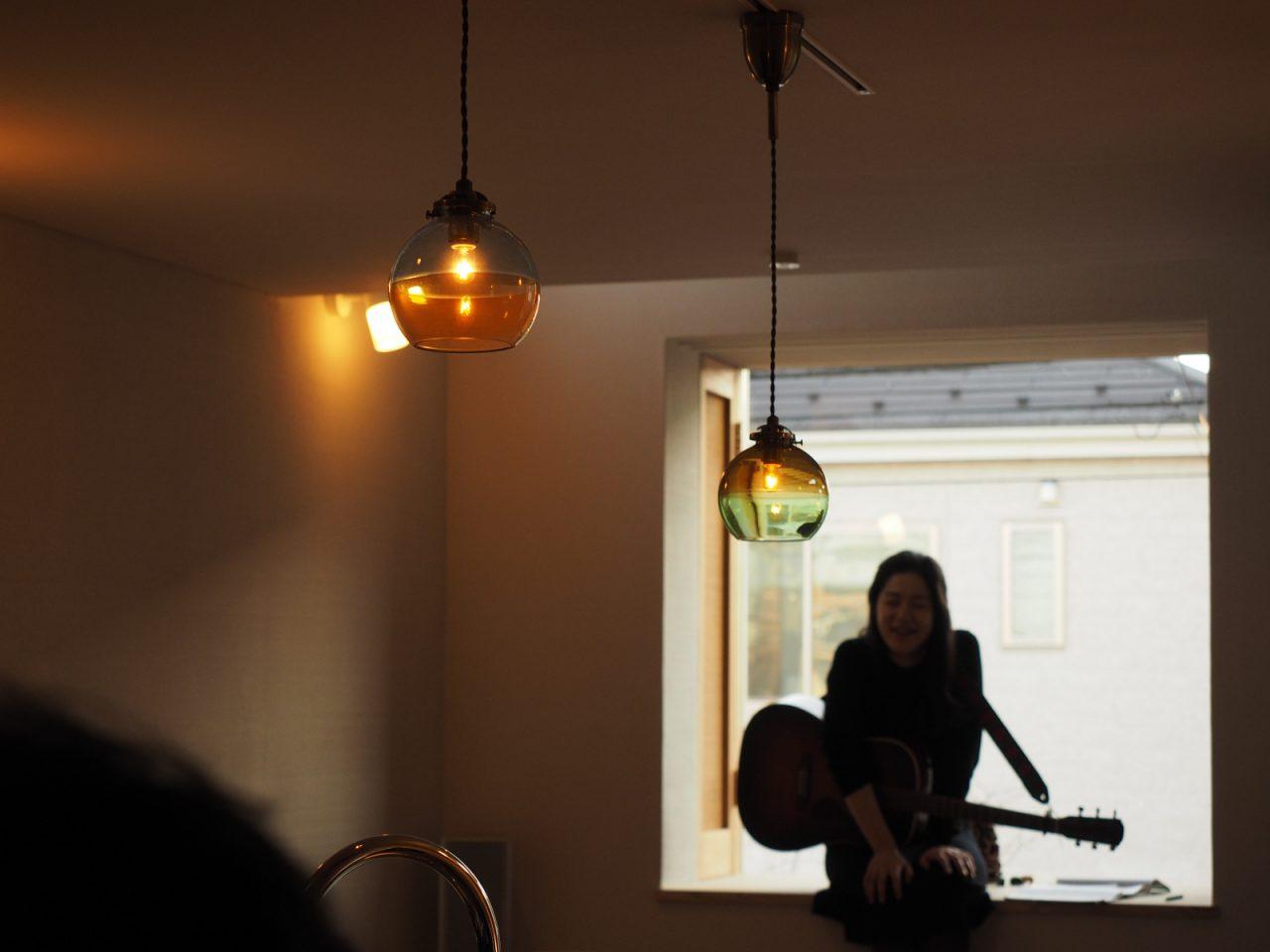 出窓に腰掛けてアコースティックギターの弾き語りをする池間由布子さん。