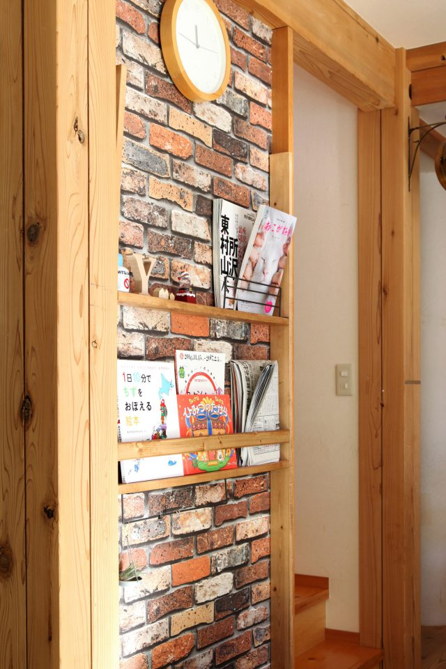 レンガ調の壁紙を貼り、その上から木の板を造り付けて本棚ラックに