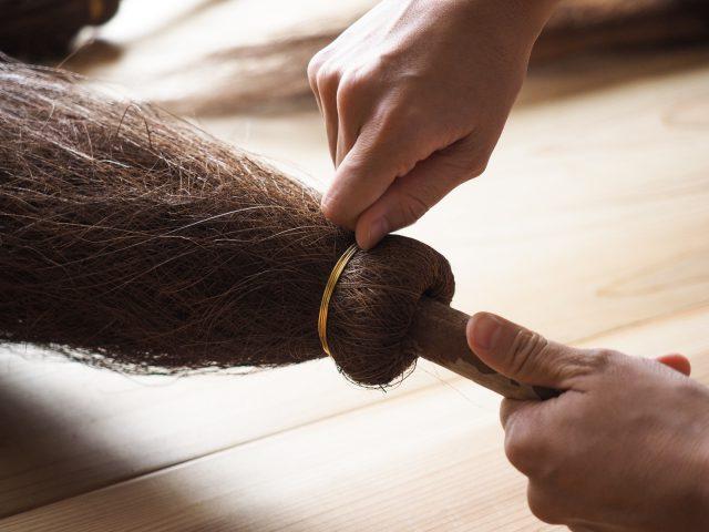 ホウキにシュロの皮を重ねながら巻きつけていき、釘や針金(真鍮製か銅製)で固定します