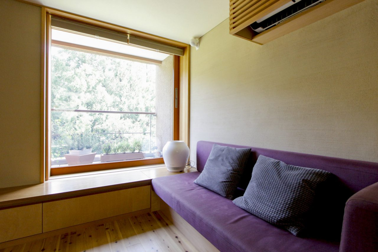 景色をより引き立てる大きな木製窓のあるリビング