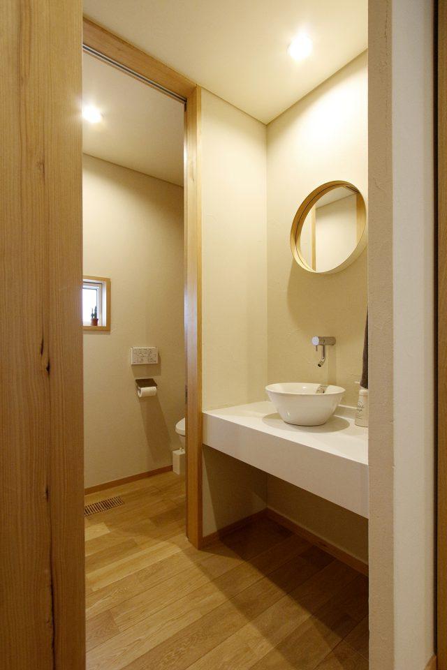 ご夫妻の出身地、岡山で作られた丸い鏡が映える洗面スペース