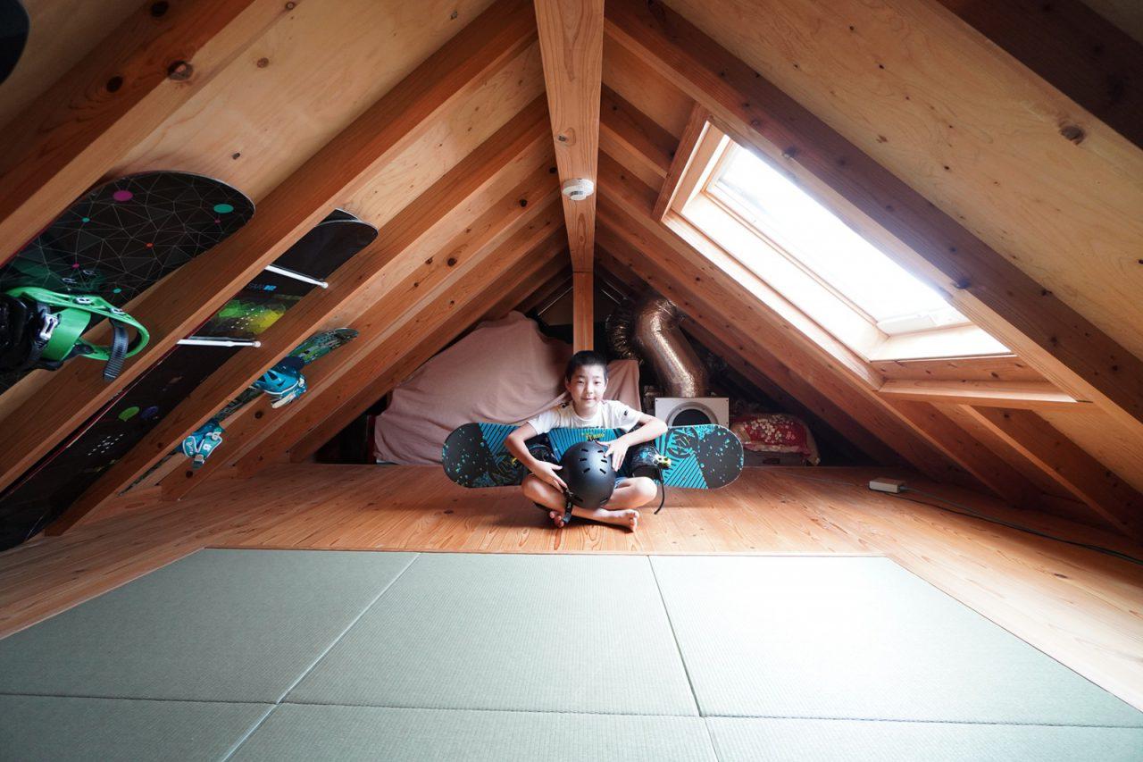 固定階段で行き来しやすくした畳敷の小屋裏。木造ドミノ住宅の三角屋根を活かしてスノーボードが収納されています。