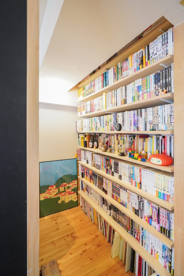 背後の本棚には、仕事や趣味の本がびっしり。