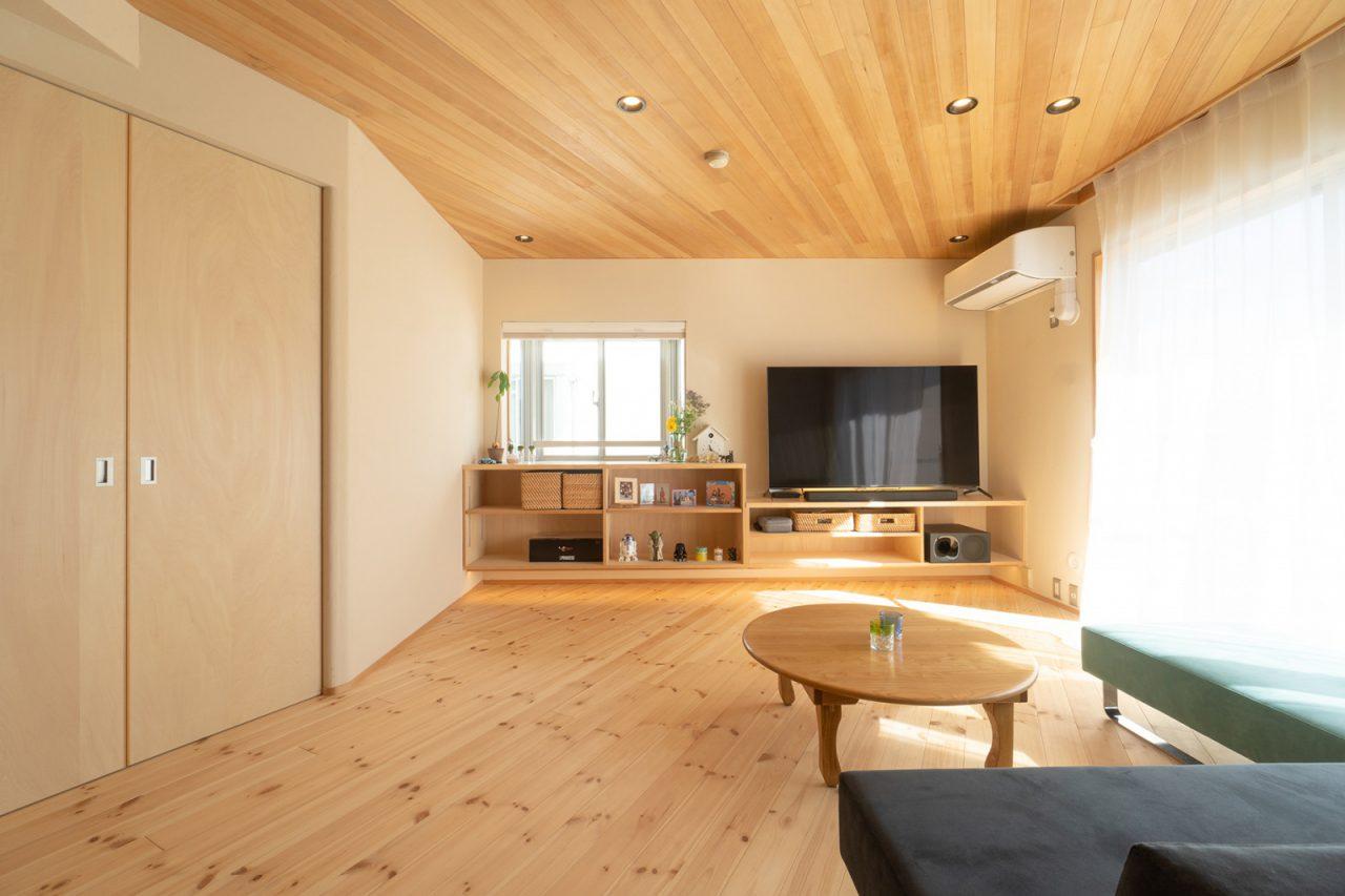 天井と床を斜めに貼ったリビング。出窓と合わせて造り付けたテレビボードもポイント。