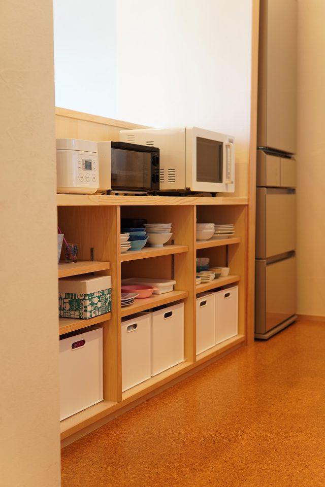 キッチンの造作収納。閉塞感がでないように高さには配慮して天井がつながるようにし、キッチン家電はしゃがまず立ったままで操作しやすい位置に。後ろにはコンセントを完備しています。