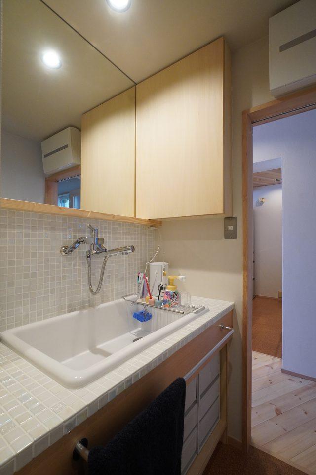 タイルの割り付けの美しい理化学用の大きな洗面台。壁収納の棚には液だれしても大丈夫なガラス板にしてあります。キッチンからの導線もスムーズ。