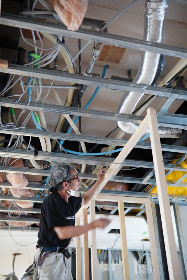 2階天井は一部が剥がされている状態で、3階床下の配管や配線が見えて、オフィスや施設の工事ならではの場面です。