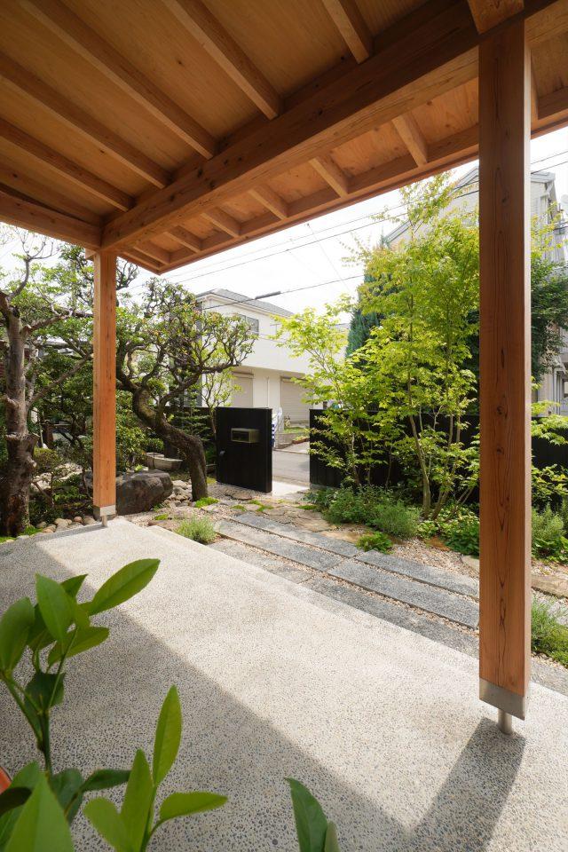 玄関前には、ラベンダーなどのハーブ類やブルーベリーなどを植栽。向かいのお宅の植栽も借景に。