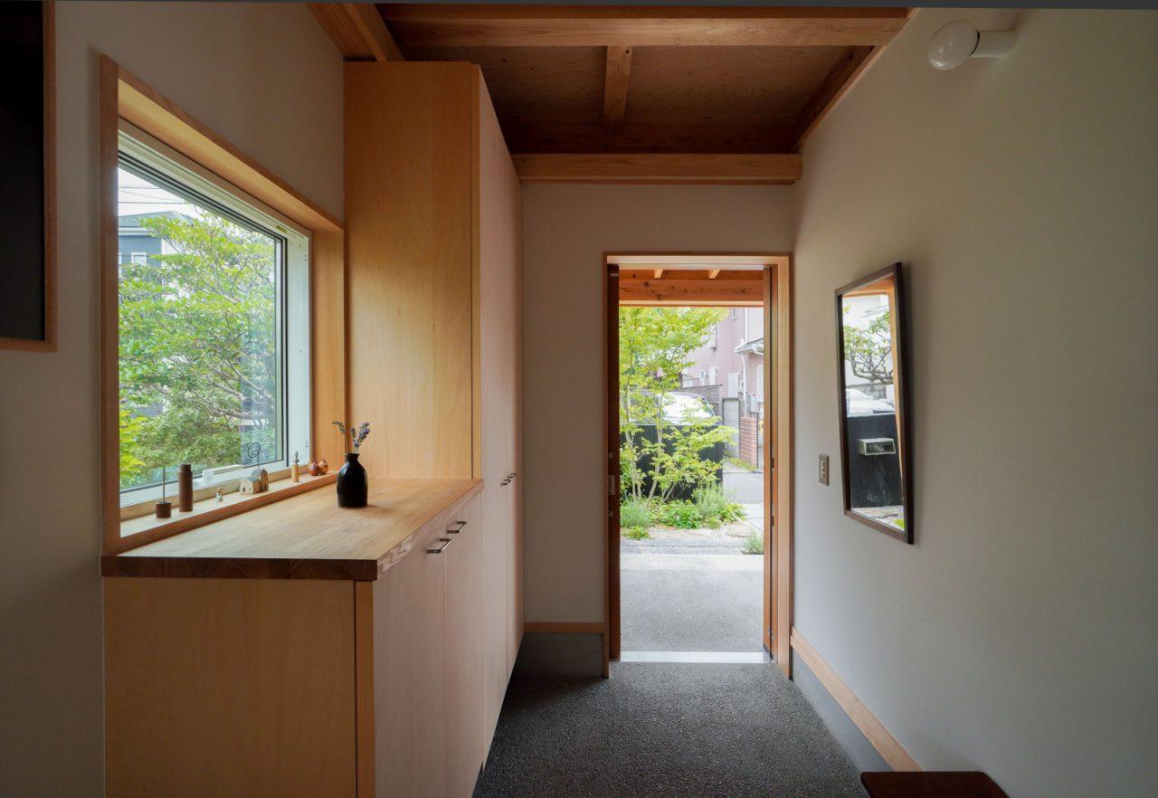 窓から庭先の緑が見え、爽やかな玄関。