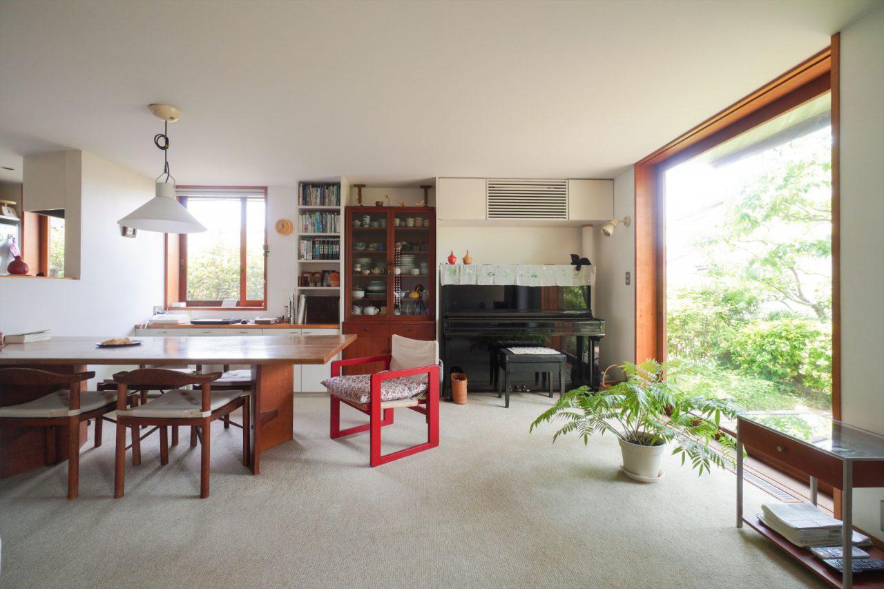木曾三岳奥村設計所のダイニングテーブルと「はんぺんチェア」は以前の家から約50年も愛用。昌民さんの恩師・吉村順三さんの「たためる椅子」の赤がアクセントに。