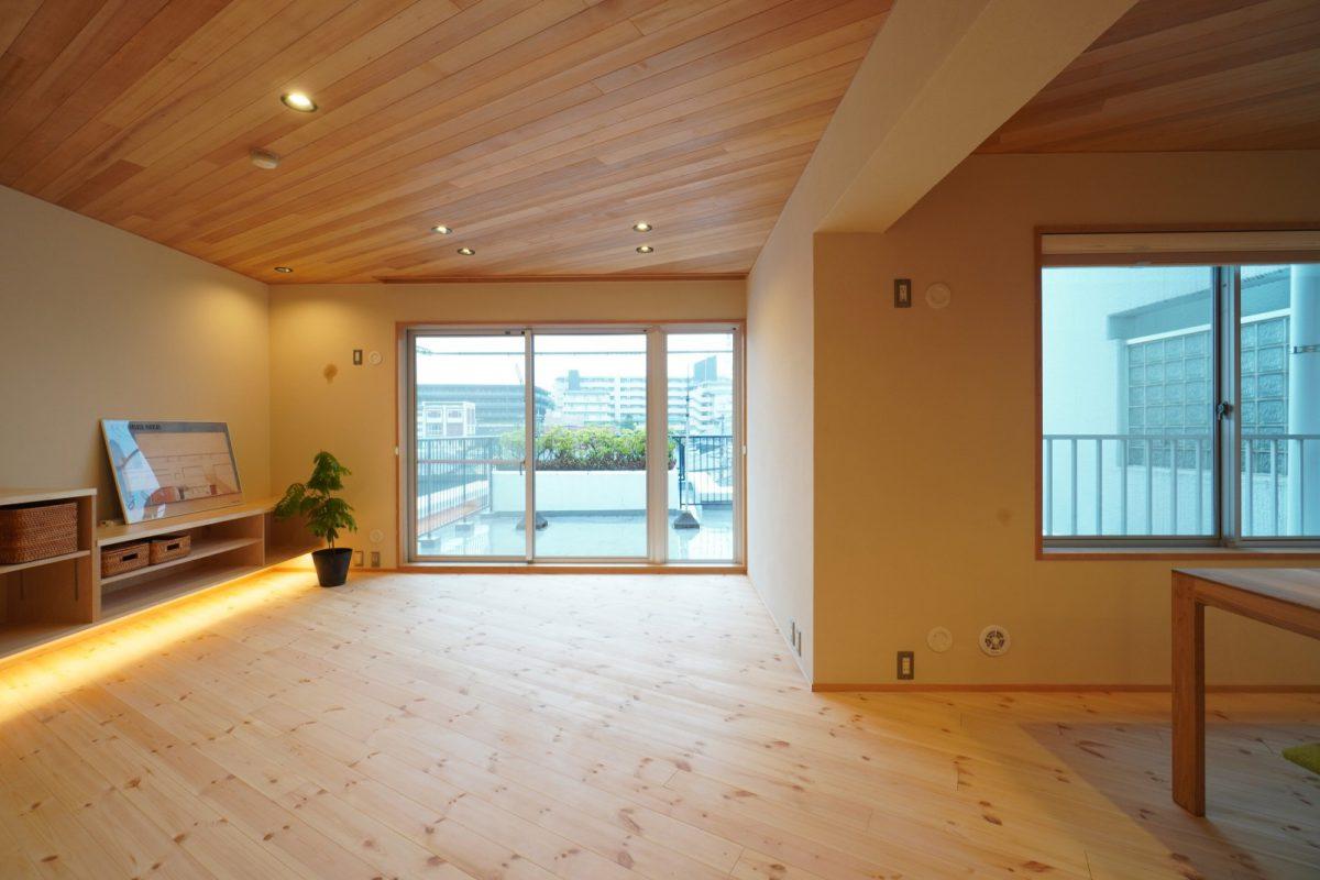 床と天井は斜め方向の板張り仕上げに。テレビボードや収納の下に間接照明を入れて浮遊感を演出