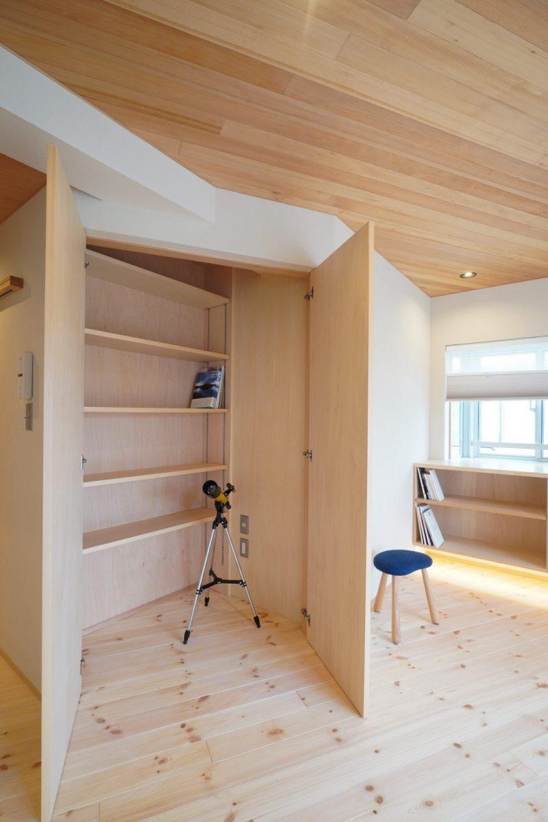 収納扉を開くと棚の手前にスペースがあり、掃除機などを充電しながら収納できる