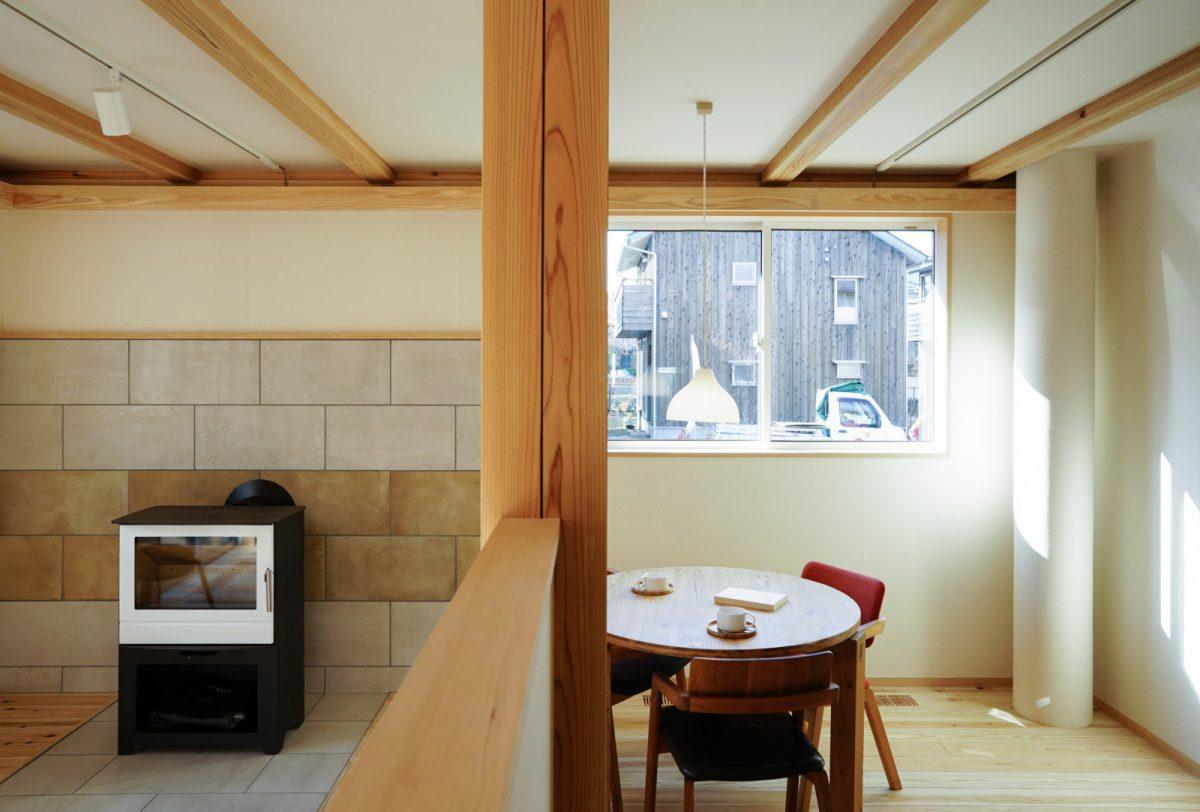 白い薪ストーブと壁面のタイルが印象的です。写真右のOMソーラーのダクトを通して屋根で集めた太陽熱を床下に送っていきます。