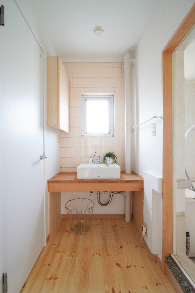 洗面台の下は配管をかくしながらタオルや衣類を収納できるスペースに。壁面の収納扉を開くと鏡が現れます。