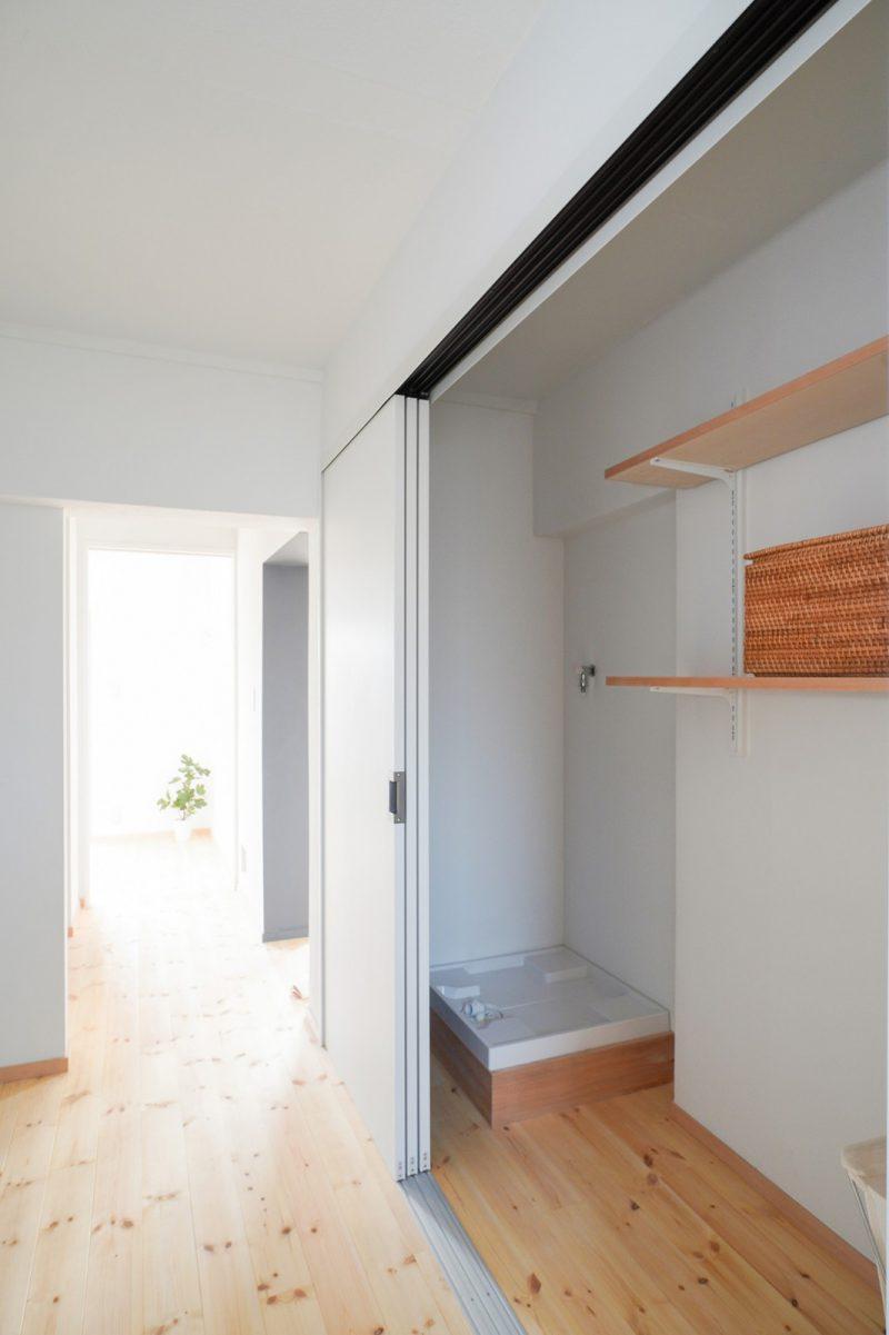 洗濯機スペースは大容量の収納と一緒に3枚引き戸ですっきりと納めました。選択時の排水を壁面裏のキッチンに接続しています。