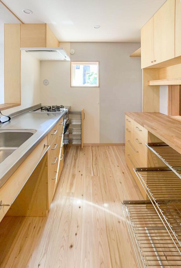 手前は鍋やフライパンを収納するのに便利なワイヤーシェルフ棚。 窓からはお隣の緑がちらっと見えていい感じです。