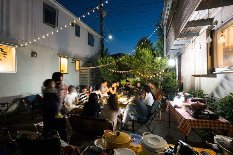 夏の夜、園路に広げたテーブルに住人が集い、語らいのひとときに花がさく。