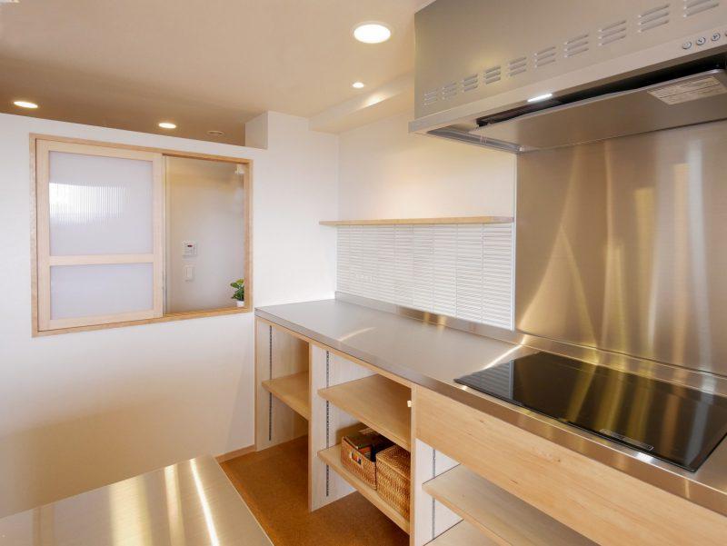 キッチンやカウンターは造作で製作。キッチンと脱衣所の間に室内窓を設けたことで光や風が室内に気持ちよく抜ける空間となっています。